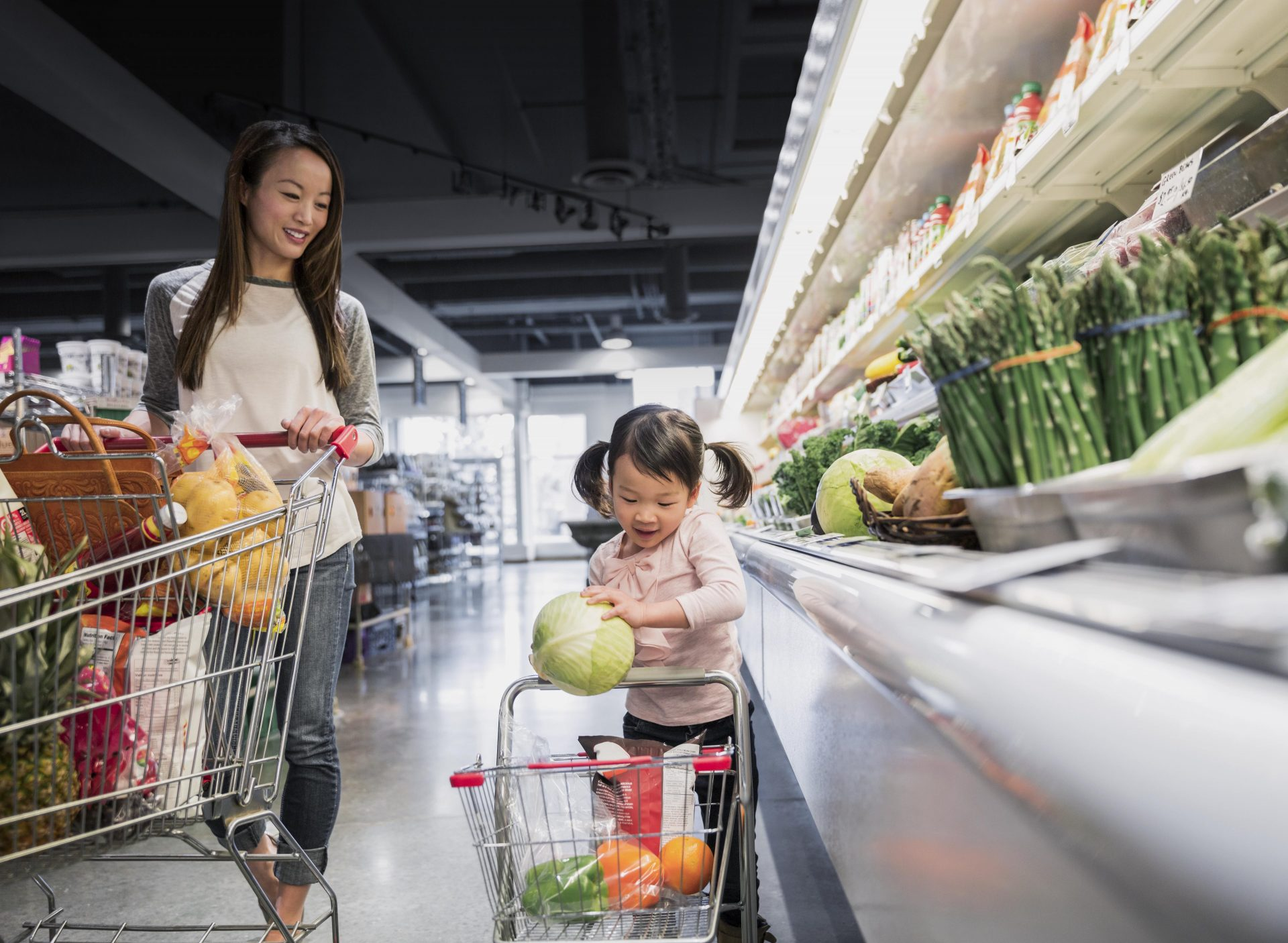 Mother Watching Daughter Place Melon In Shopping Cart